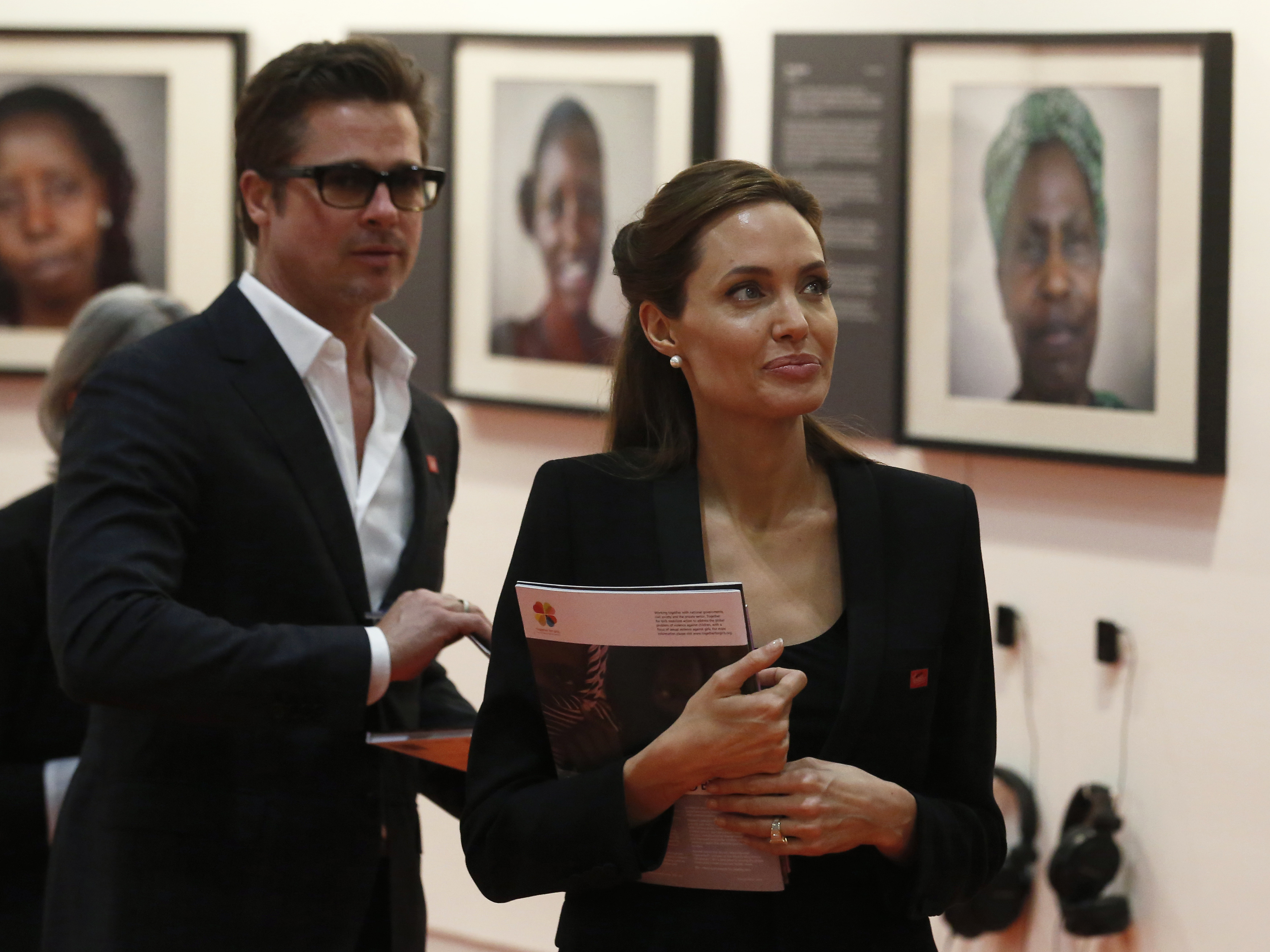 Actress and campaigner Angelina Jolie and her partner, actor Brad Pitt look at photographs at a fringe event of a summit to end sexual violence in conflict at the Excel centre in London